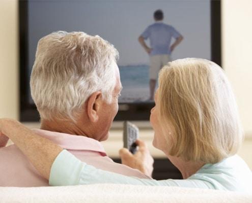 casal a assistir televisao com volume muito alto