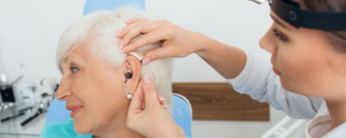 mulher a colocar aparelho auditivo